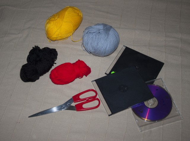 Нам понадобятся нитки, можно взять 100%акрил, они совсем не дорогие.Есть такая пряжа детская.Желательно ,что бы нитки были одной толщины.4 цвета:жёлтый, чёрный,красный ,серый.5 коробочек от сд диска(можно заменить картоном,причём размер по ширине вы можете выбрать произвольно.Но,чтобы для всех 4 цветов был одинаков).Размер моей коробки 12см на 14см.Еще будет нужна ленточки,стразы для глазок и семечки для клювиков и клей.