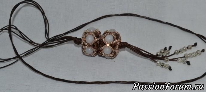 две бусины плетеные. Шнур коричневый тройной. Узелки. На концах шнура металлические бусины.