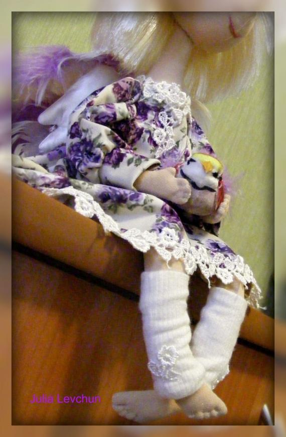 Эта малышка в наряде сиреневого ,лавандового цвета. Крылышки выполнены из двух видов перьев - белых остевых и сиреневых пуховых. В руках держит стеклянную баночку с лавандовым маслом