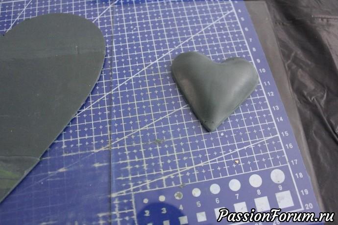С помощью металлической формочки сердца делаю маленькое сердце. Для этого надо раскатать два пласта глины, наложить на формочку так, чтобы оно провисло внутри- помогаем пальцами глину внутрь, сверху кладем второй пласт ровно, формочку ставим на стол и выдавливаем сердечко. Оно получается выпуклым.