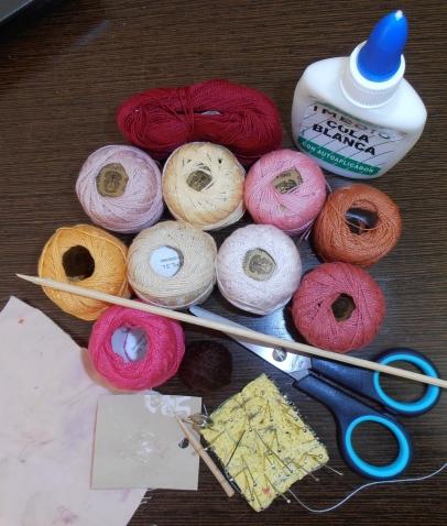 Нужен крючок для вязания, разноцветные нитки, ножницы, клей, портные булавки, палочка, тряпочка, пористый картон.