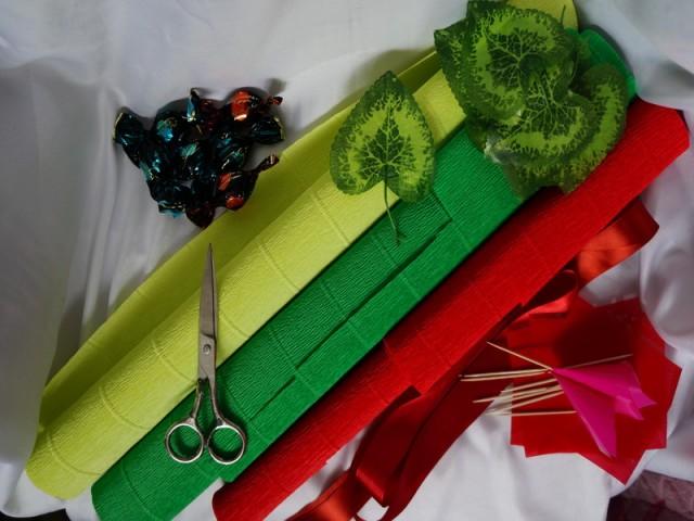 Гофробумага: зелёная, красная, салатовая. Зубочистки или шпажки. Конфеты-марсианка, искусственные листики, бумага для букетов для фунтиков, бусинки по желанию, атласная лента для декорирования корзинки. Клей пистолет. Пенопласт или монтажную пену, или пеноплекс для крепления конфет