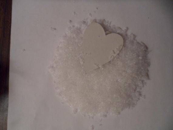 Вырезаем сердечки, мажем клеем и опускаем в нашу горку измельченного полиэтилена.