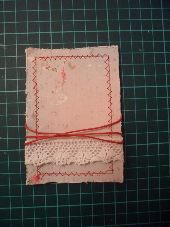 Приклеиваем на скрап бумагу кружево и наматываем вощеный шнур.
